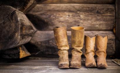 Zwei Paar Cowboystiefel stehen auf Holzboden nebeneinander
