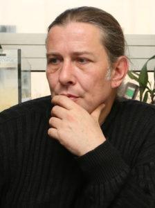 Markus Baur, der Leiter der Reptiliensation München, im schwarzen Pulli, die langen Haare zum Zopf gebunden,