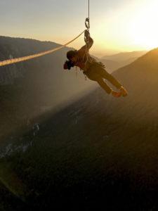 Der Regisseur und Kameramann Jimmy Chin hängt während des Filmdrehs von Free Solo im Seil. Im Hintergrund geht über dem Yosemite Valley die Sonne unter.