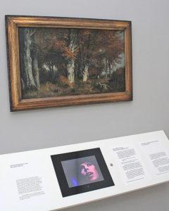 Im Lenbachhaus: Landschaftsmalerei aus dem 19. Jahrhundert darunter ein kleiner Bildschrirm mit Filmausschnitt, in dem Schlagersängerin Alexandra singt.