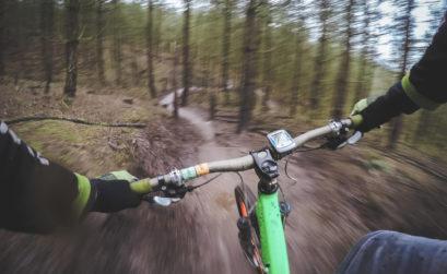 Ein Mountainbiker fährt auf einem Trail durch den Wald. Das Foto ist aus der Perspektive des fahrenden Mountainbiker aufgenommen.rs