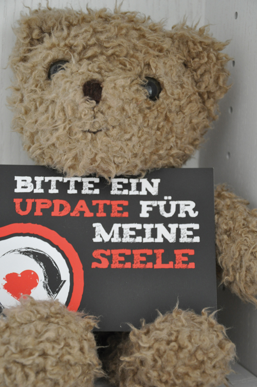 """Teddy-Bär hält ein Schild mit der Aufschrift """"Bitte um ein Update für meine Seele"""""""