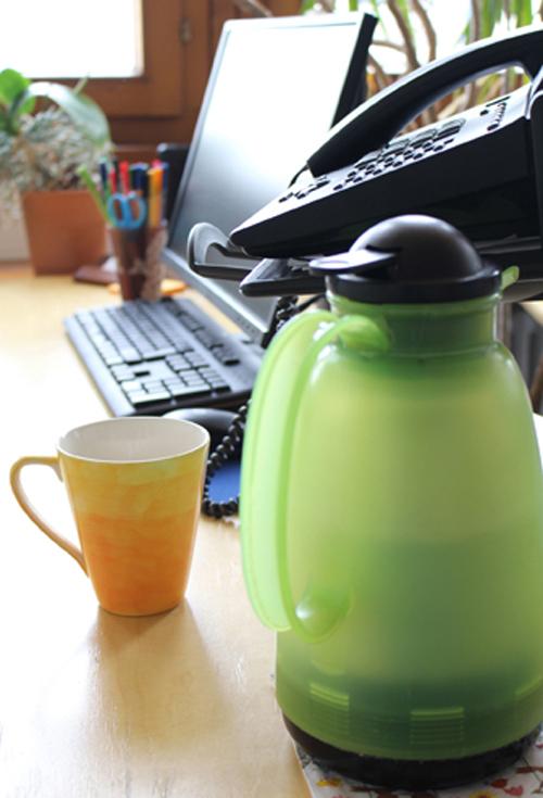 Grüne Teekanne und gelbe Tasse auf einem Schreibtisch bei der TelefonSeelsorge