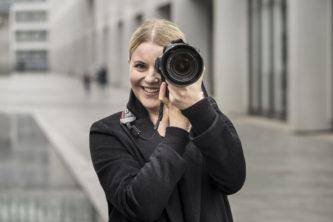 Junge Frau frontal mit Fotoapparat