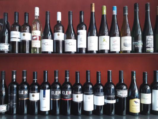 Ein mit Rotweinflaschen gefülltes Weinregal: Die Auswahl ist groß.