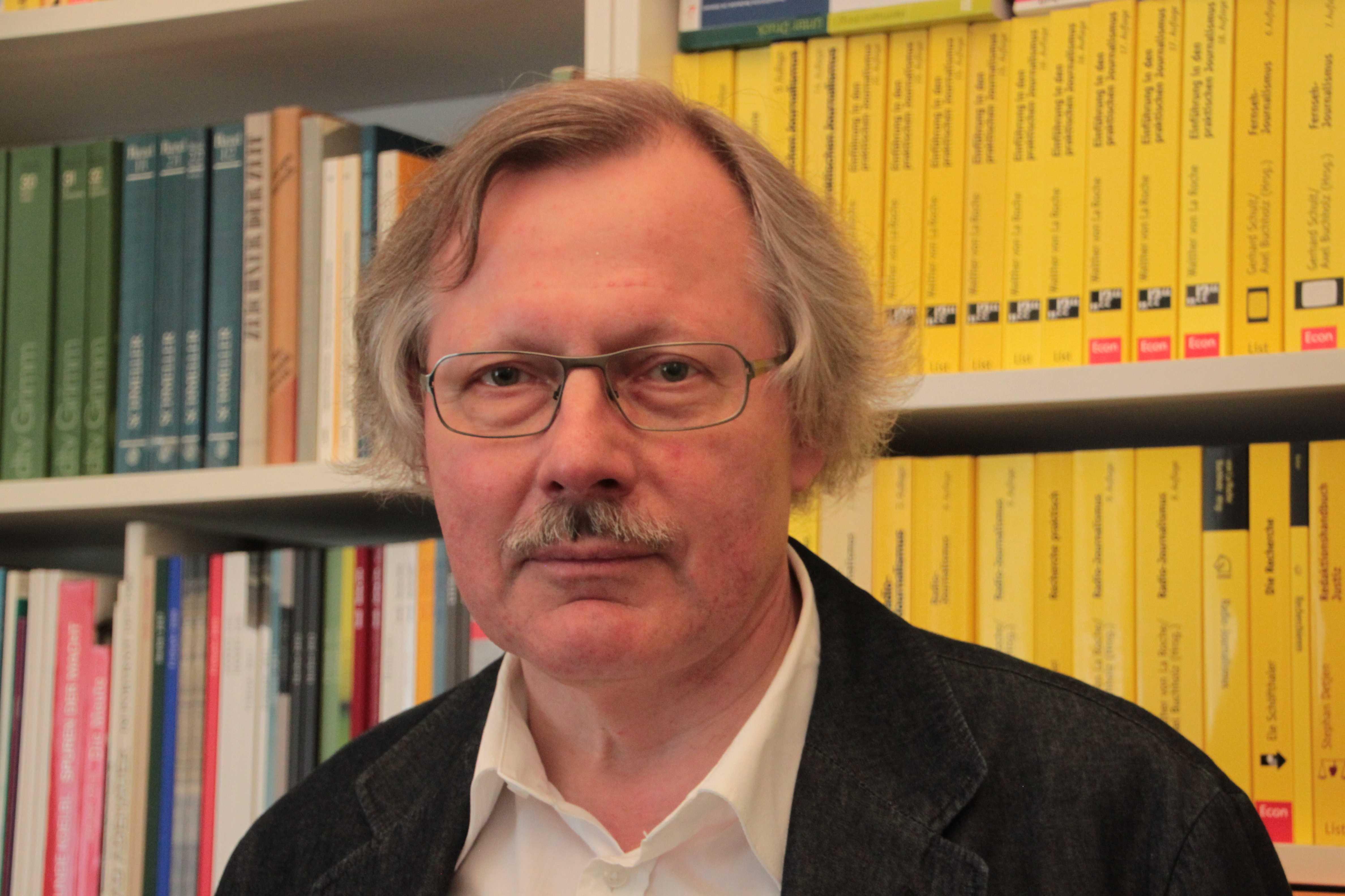 Peter Lokk, Leiter der Journalistenakademie vor einer Bücherwand