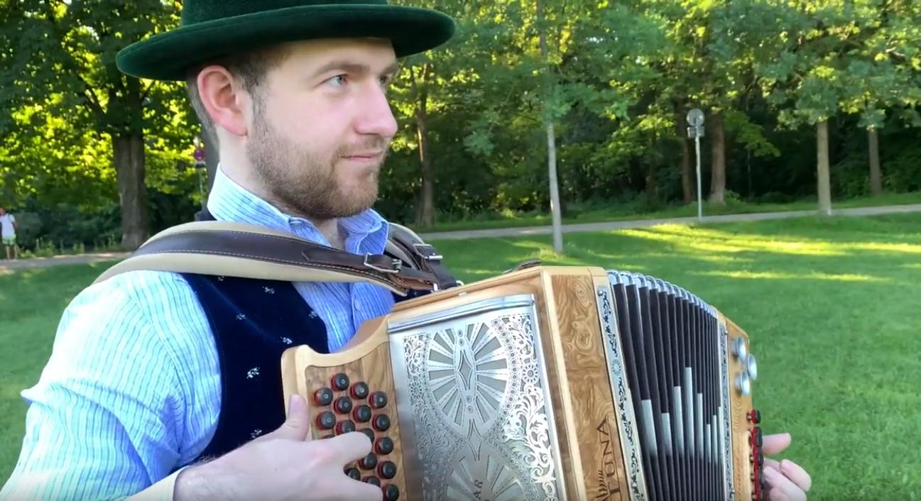 Ein Mann in bayerischer Tracht spielt Akkordeon.
