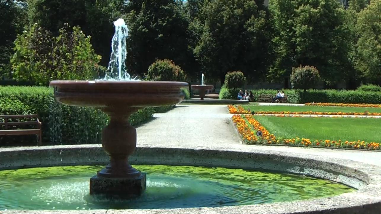 Zwei Brunnen verbunden durch einen Weg, dazwischen sind Blumenbeete, Rasenflächen und Hecken zu sehen.
